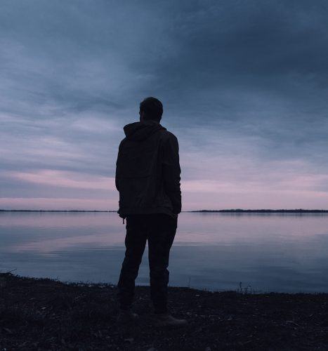 Man standing at edge of sea in sunset