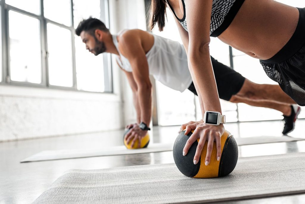 Young sportive couple exercising with medicine balls on yoga mats